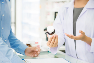 pharmacist holding medicine bottle giving advice to customer