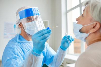 medical worker testing senior woman