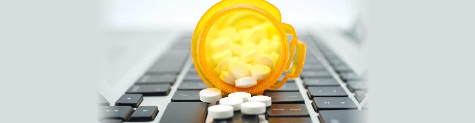 Online prescription order concept with bottles of medicine on keyboard